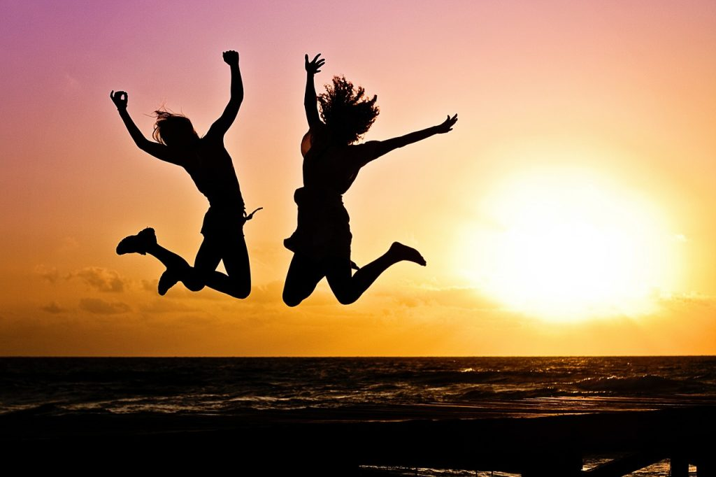 Young people leaping on the beach at sunset
